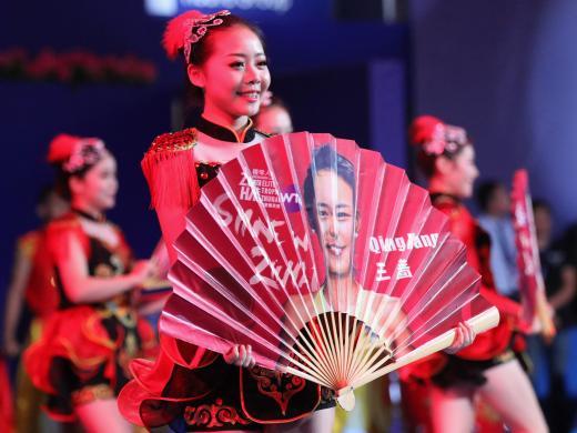 A dancer displays a fan bearing the face of Wang Qiang (Getty)